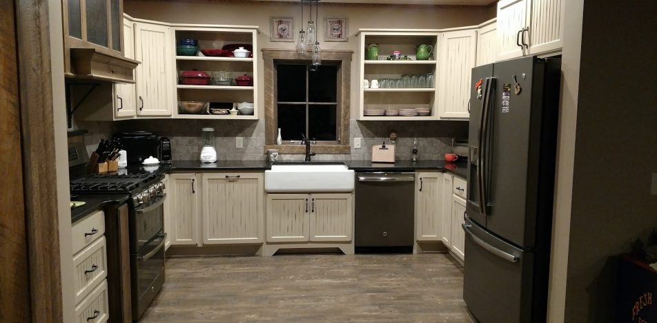Rub through Paint with antiquing and Rustic Alder bead board cabinets combined with Stained hood with hammered wrought iron inserts.