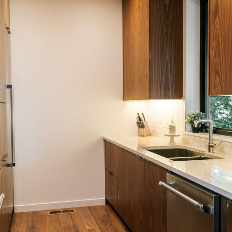 frameless vertical grain walnut kitchen with quartz countertop and undermount sink.
