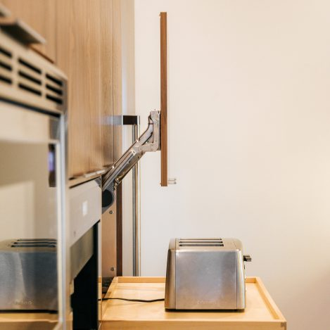 frameless walnut cabinet with lit up door and rollout Toaster Storage