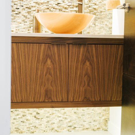 inset floating walnut vanity with quartz counter and vessel sink.