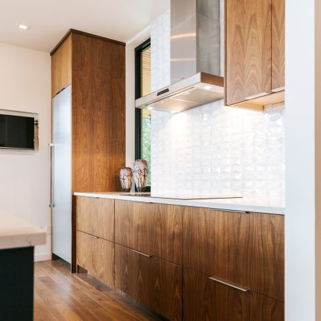 frameless vertical grain walnut kitchen with quartz countertop and Thermador hood.
