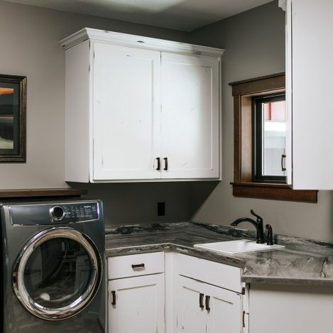Laundry room with Rustic Alder painted white cabinets with rub thru