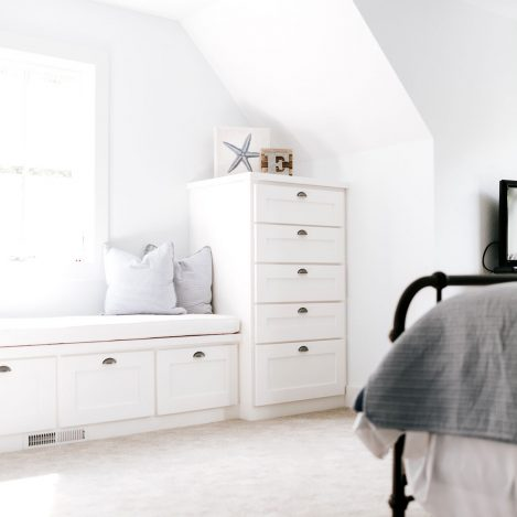 White shaker style bench under window with stack of drawers on the side