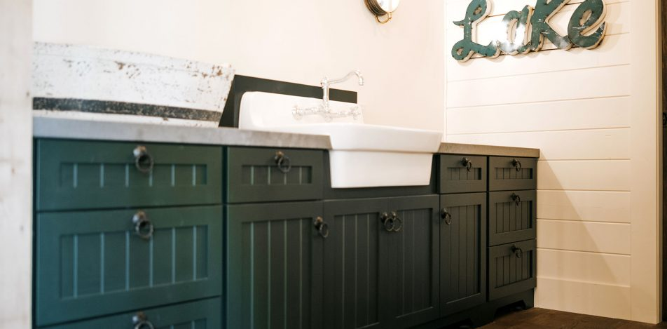 Full Overlay v-groove cabinets painted studio green with farm sink
