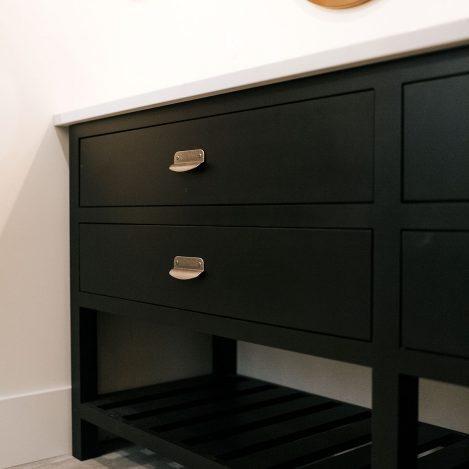 Inset vanity cabinet painted Tricorn Black with slatted wood shelf