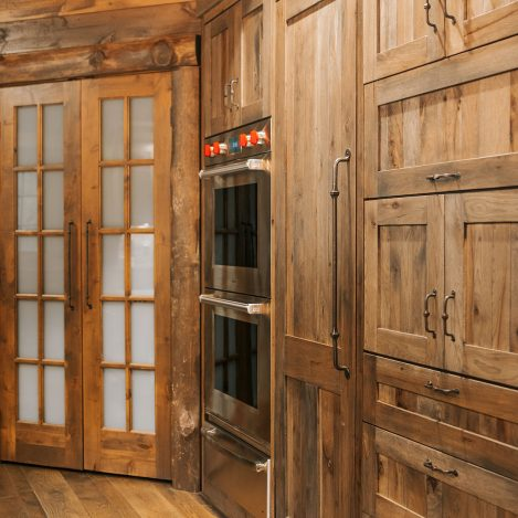 Distressed Rustic Hickory wall cabinets with double wall oven, panel ready freezer and appliance pullout