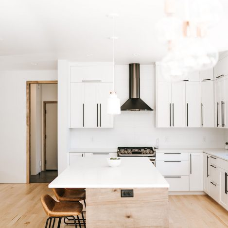 Two toned Kitchen with white perimeter cabinets, rustic soft maple book matched horizontal grain island