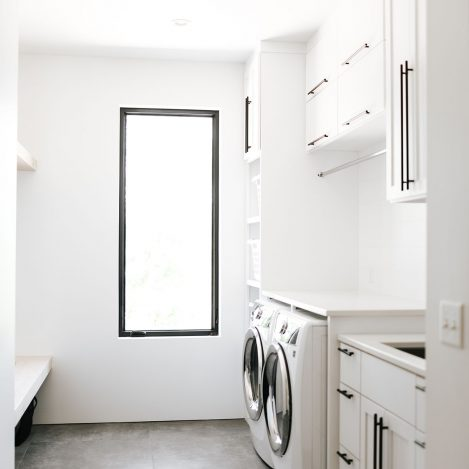 Shaker style white laundry cabinets with black bar pulls and folding surface